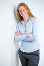 Confident young business person a manager or assistant leaning against a wall and smiling at the camera Stock Image