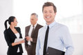 Confident young businessman cheerful men in formalwear holding clipboard and smiling while his colleagues talking on background Royalty Free Stock Photos