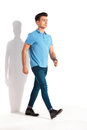 Confident young casual man in polo shirt and jeans walking