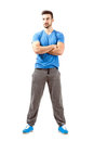 Confident young fit male with folded hands looking away full body length isolated over white background Royalty Free Stock Photos