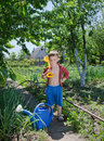 Confident young gardener small boys stands with his watering can spade slung over shoulder in amongst vegetables garden facing Royalty Free Stock Image