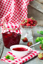 Confiture with strawberries and basil on a wooden background Royalty Free Stock Photos