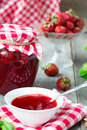 Confiture with strawberries and basil on a wooden background Stock Photos