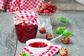 Confiture with strawberries and basil on a wooden background Stock Photo