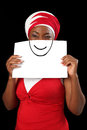 Conflicting expressions be true to yourself angry african woman dressed in a red dress with fitting headscarf holding a paper with Stock Photography
