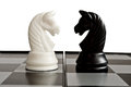 Confrontation of black and white knights on the chessboard Royalty Free Stock Photos