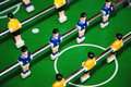 Confrontation table football the between the blue and yellow team board game green field diagonal composition of the shot Stock Photo