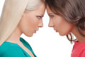 Confrontation two angry women standing face to face with their foreheads touching and looking at each other while isolated on Royalty Free Stock Photo