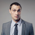 Confused businessman on gray background young Royalty Free Stock Photos
