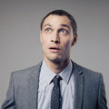 Confused businessman on gray background young Royalty Free Stock Photography