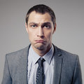 Confused businessman on gray background young Royalty Free Stock Image