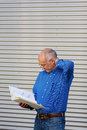 Confused businessman reading binder against shutter mature while standing Royalty Free Stock Images