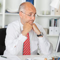 Confused businessman staring at computer at office desk mature while leaning on Stock Photography