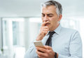 Confused businessman using a smart phone with hand on chin having troubles Stock Photo