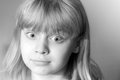 Confused little blond girl monochrome portrait of Royalty Free Stock Photo