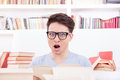 Confused student with glasses  surrounded by books Royalty Free Stock Images