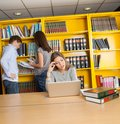 Confused student looking at laptop in university female library Royalty Free Stock Images