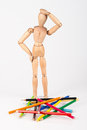 Confused wood mannequin standing at heap of colour pencil isolat isolated on white background Royalty Free Stock Images
