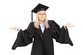 Confused young female in graduation gown isolated on white background Stock Photos