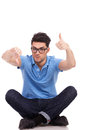 Confused young man thumbs up and down Royalty Free Stock Photo