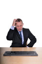 Confusion image of abusinessman at a desk looking confused Royalty Free Stock Photography