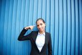 Confusion image of young businesswoman standing by blue wall Stock Photo