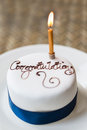 Congratulations cake a small and single candle the has written on it Royalty Free Stock Images