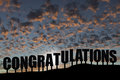 Congratulations the word on a hillside silhouetted with puffy clouds Stock Photos