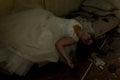 Conjugal creepy crime bride lying in devastated room Stock Photo