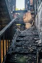 Consequences of fire in apartment house. Burnt interior. Burnt wooden staircase Royalty Free Stock Photo