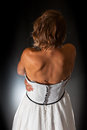 Considerations of a bride retro seen from the back in deep thoughts she wears white silk dress with black embroidery she is Stock Image