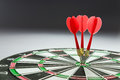 Consistency three red darts pinned right on the center of dartboard Royalty Free Stock Images