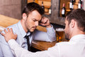 Consoling friend frustrated young men in shirt and tie being consoled by his in bar Royalty Free Stock Image