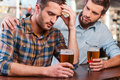 Consoling his depressed friend young men sitting at the bar counter and holding head in hand while being consoled by sitting near Royalty Free Stock Image