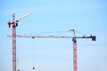 Constraction cranes pair of against blue sky Royalty Free Stock Images