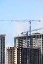Constraction cranes view of house building with against blue sky Stock Photo