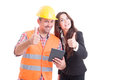 Construction builder and business woman standing back to back modern women using wireless tablet showing like or thumbs up gesture Royalty Free Stock Images