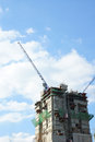 Construction building with crane against blue sky Stock Images