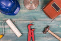 Construction concept. Roller, hammer, hard hat, red adjustable pipe wrench, circular saw blade and welding mask on nice green wood Royalty Free Stock Photo