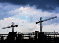 Construction crane silhouettes and blue cloudy sky Royalty Free Stock Image
