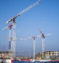Construction cranes on a blue sky background begin to build new residential complex with industrial smog Stock Images