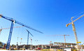 Construction cranes on a building site architectural background of an urban against blue sunny sky Stock Image