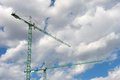 Construction cranes two big with a background of blue sky with white clouds Stock Image