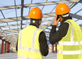 Construction engineers engineer with safety vest discussion on location site Royalty Free Stock Image