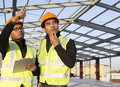 Construction engineers with safety vest discussion on location site Stock Image
