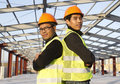Construction engineers standing with safety vest looking at the camera Stock Photo