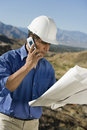 Construction foreman with cellphone and blue print on site in hardhat using mobile phone while looking at Royalty Free Stock Image