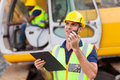 Construction foreman walkie talkie talking on holding clipboard Royalty Free Stock Photo