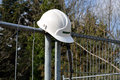 Construction hard hat on fence Stock Image