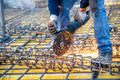Construction industry details - worker cutting steel bars using angle grinder mitre saw. Royalty Free Stock Photo